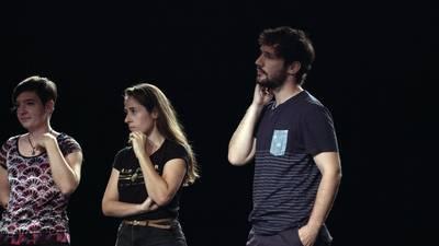 Zine-zuzendaria atzeko hiru aktoreei paperak banatzen